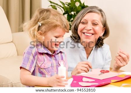 Grandmother with granddaughter playing together glue hearts on paper - stock photo