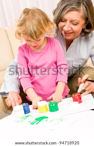 Grandmother with granddaughter playing together paint hand-prints on paper - stock photo