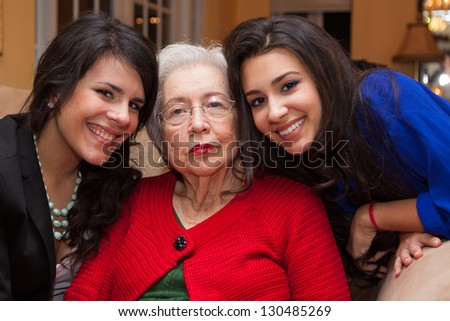 Grandmother with granddaughters in a home setting.