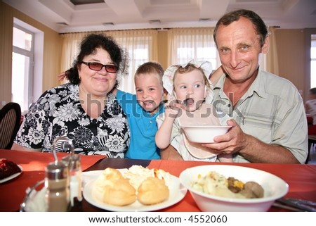 Grandmother with grandfather behind table with grandson and granddaughter - stock photo
