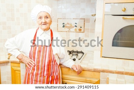 Grandmother with hat and apron in her kitchen. - stock photo
