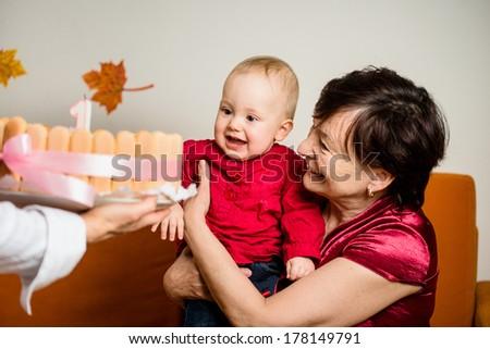 Grandmother with her baby grandchild celebrating first birthday - stock photo