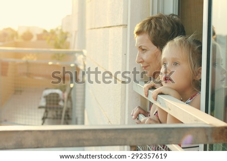 grandmother with her grandchild looking from the window - stock photo