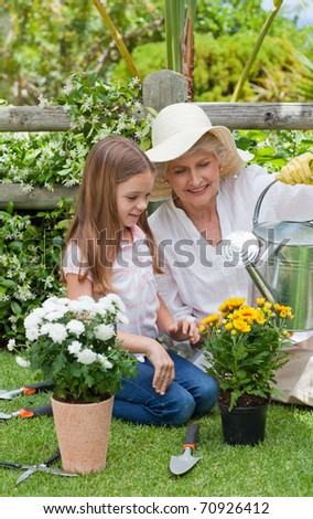 Grandmother with her granddaughter working in the garden - stock photo