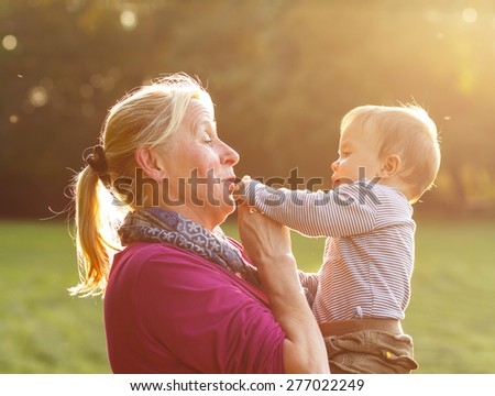 Grandmother with her grandson playing in the park - stock photo