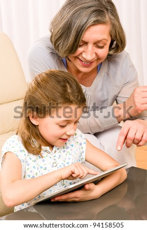 Grandmother with young girl use touch screen tablet computer smiling - stock photo