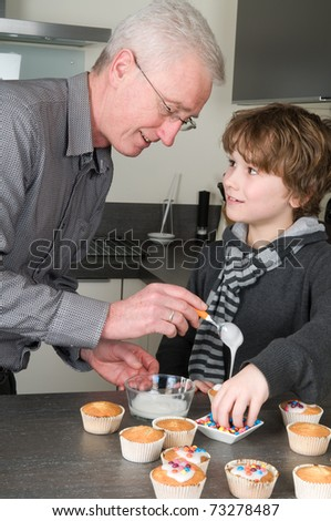 Grandpa and child are decorating the just baked cupcakes