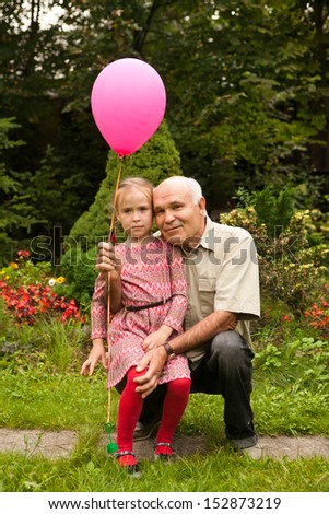 grandpa and grand daughter in the summer garden with pink balloon - stock photo