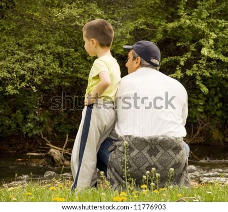 grandpa and grandson enjoying the sun - stock photo
