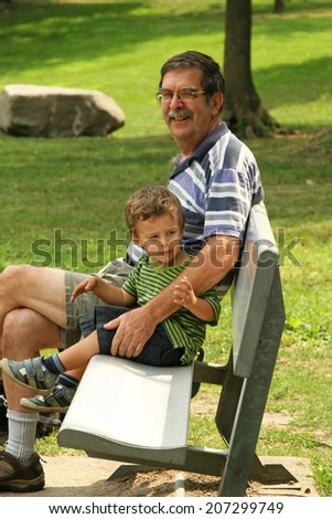 Grandpa and grandson sitting on park bench