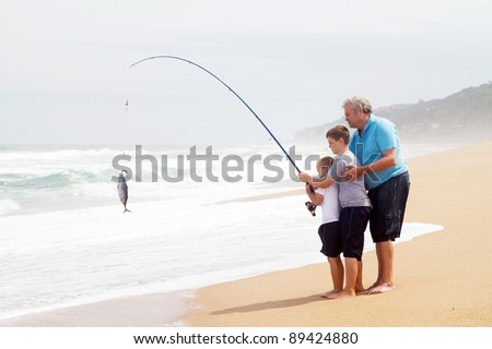 grandpa and grandsons together pulling a fish out of water - stock photo