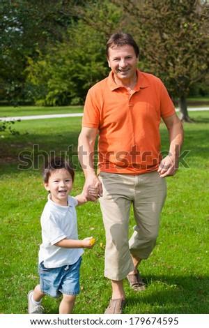 Grandpa and his grandson are having fun in the park. - stock photo