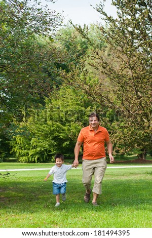 Grandpa and his grandson are running an having fun in the park. - stock photo