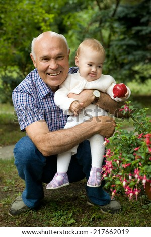 grandpa and his little  grand daughter in the summer park - stock photo