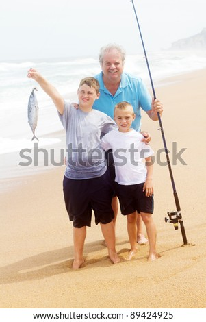 grandpa and two grandson catching a big fish on beach - stock photo