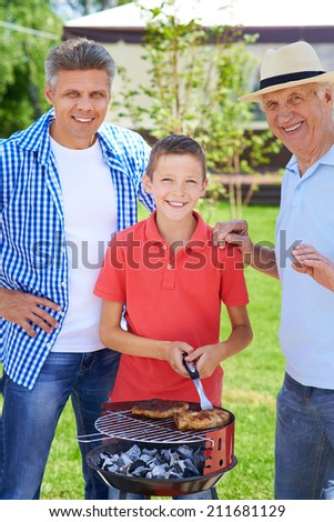 Grandpa, father and boy grilling sausages - stock photo