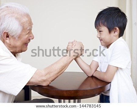 grandpa hand wrestling with grandson.