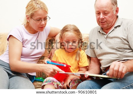 Grandpa, mother and grand-daughter reading and playing - stock photo