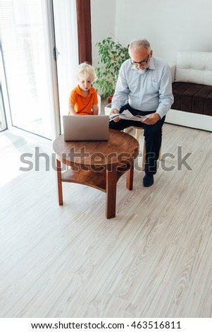 Grandpa reading newspaper laptop while grandson using laptop in the living room