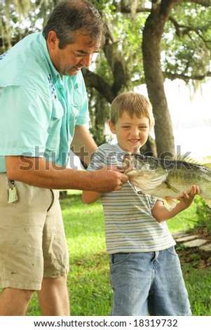 Grandpa showing how to hold a fish - stock photo