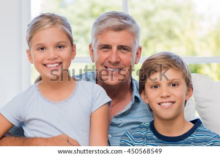 Grandpa sitting with boy and girl looking at camera. Cheerful Grandfather embracing grandson and granddaughter on couch. Portrait of smiling grandchildren with older man. - stock photo