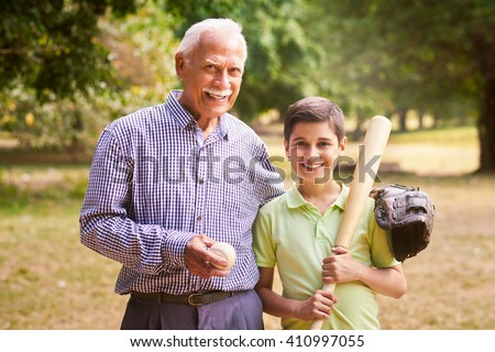 Grandpa spending time with grandson: Portrait of senior man playing baseball with his grandchild in park. The old man embraces the young kid holding the bat, smiling and looking at camera - stock photo