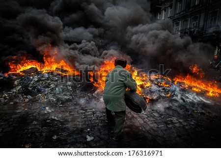 Grandpa throws a tire into the fire, to defend against attack police. Ukraine, Kiev (01.23.2014)