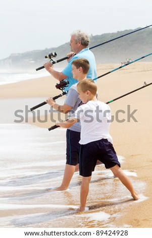 grandpa took his grandsons fishing on beach: ready to cast the fishing line - stock photo