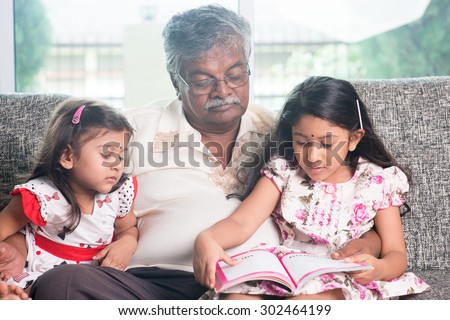 Grandparent and grandchildren reading story book. Happy Indian family at home. Asian grandfather and granddaughters indoor lifestyle. - stock photo