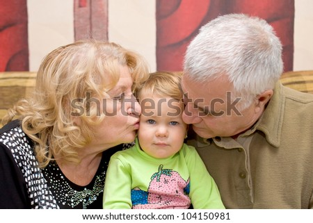 Grandparents - adorable amorous happy senior couple kissing baby
