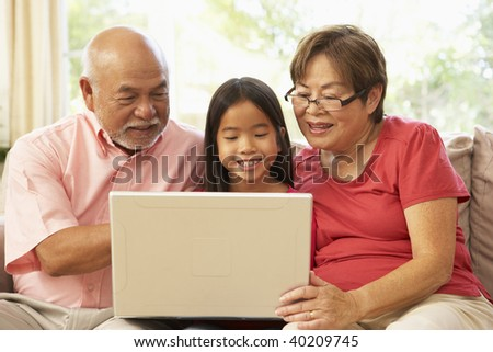 Grandparents And Grandaughter Using Laptop Computer At Home - stock photo