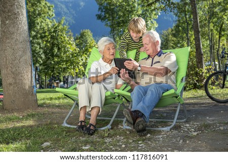 Grandparents and grandchild using their tablet computer while camping - stock photo