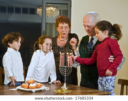 grandparents and grandchildren lightening Menorah  together - stock photo