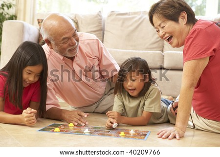 Grandparents And Grandchildren Playing Board Game At Home - stock photo