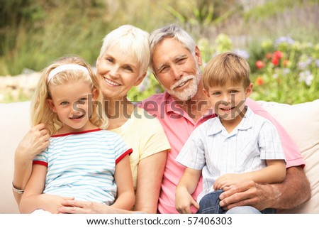 Grandparents And Grandchildren Relaxing In Garden - stock photo