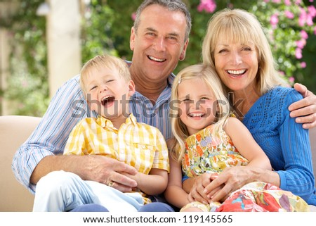 Grandparents And Grandchildren Sitting On Sofa Together - stock photo