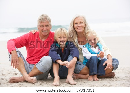 Grandparents And Grandchildren Sitting On Winter Beach Together