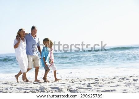 Grandparents and Grandchildren Walking Along Beach - stock photo