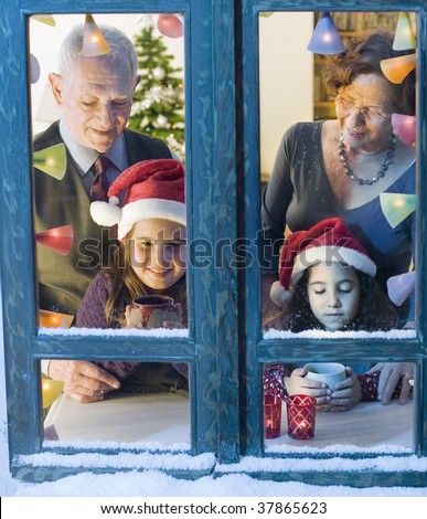 Grandparents and granddaughter at the window on Christmas eve. - stock photo