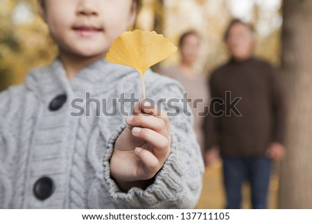 Grandparents and granddaughter in park - stock photo