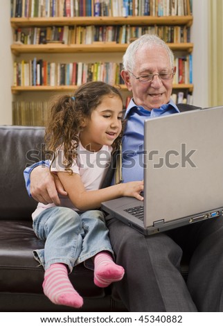 grandparents and granddaughter with laptop computer at home - stock photo