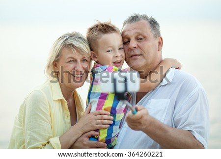 Grandparents and grandson making phone selfie - stock photo
