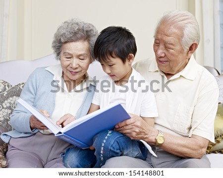 grandparents and grandson reading a book together. - stock photo