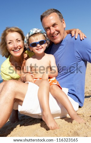 Grandparents And Grandson Sitting On Beach - stock photo