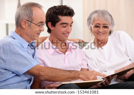 Grandparents and grandson watching photo album