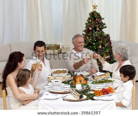 Grandparents and parents tusting in a Christmas dinner at home - stock photo