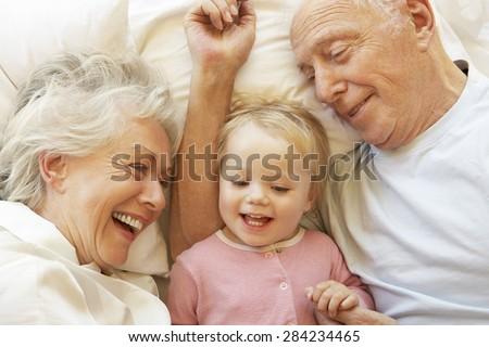 Grandparents Cuddling Granddaughter In Bed - stock photo