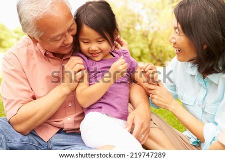 Grandparents Cuddling Granddaughter In Park - stock photo