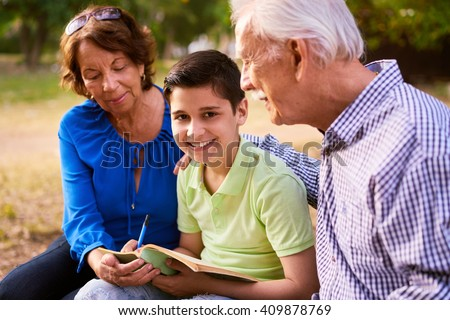 Grandparents educating grandson: Senior woman and old man spending time with their grandchild in park. The old people help the preteen boy doing his school homework. The kid looks at camera - stock photo