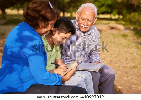 Grandparents educating grandson: Senior woman and old man spending time with their grandchild in park. The old people help the preteen boy studying and doing his maths homework - stock photo
